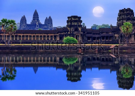 Angkor Wat Temple complex view at the main entrance, located near Siem Reap, Cambodia. Late night with the full Moon at the sky reflecting in the water - stock photo
