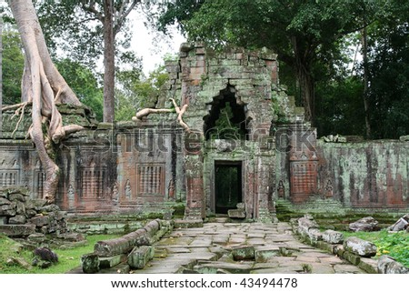 Angkor Wat temple complex with trees overgrowing the ruins in Cambodia.