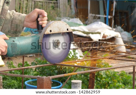 Angle Grinder Metal sawing with flashing sparks close up and Repairman hands home repair garden working summer time. Also called Circular Saw handheld electric instrument - stock photo