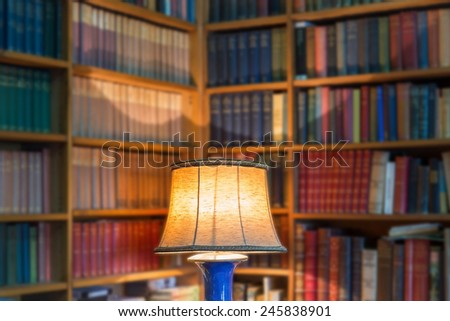 Angle library of old books and knowledge. The lamp shade in the foreground. - stock photo