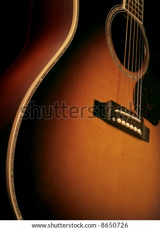 Angle shot of a maple wood acoustic guitar showing wood grain, bridge and strings. - stock photo