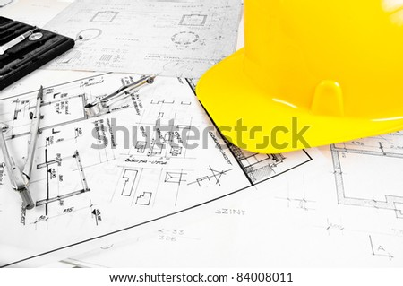Angle shot of some construction plans and a yellow helmet - stock photo