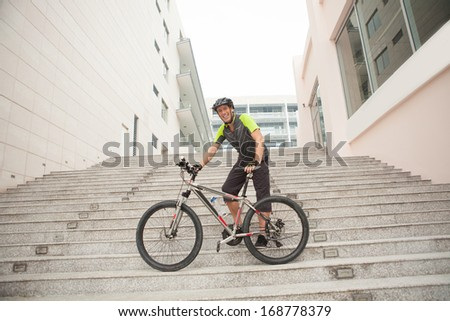 Angle view of a smiling cyclist standing near his modern bicycle on the upstairs  - stock photo
