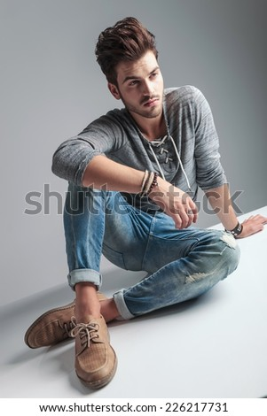 Angle view of a young casual fashion man sitting on the floor while looking away from the camera. - stock photo