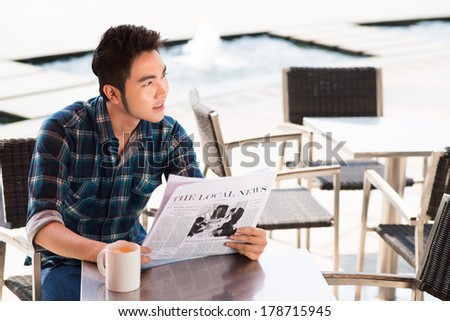 Angle view of a young man reading the newspaper at cafe  - stock photo