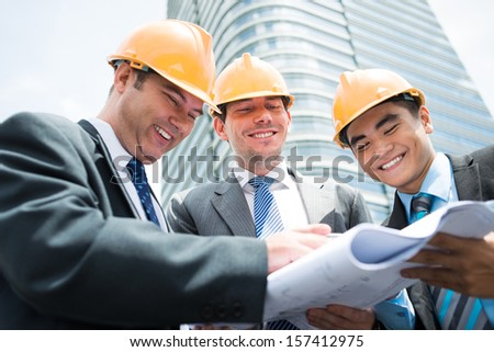 Angle view of cheerful young engineers discussing the project of the building on the foreground - stock photo