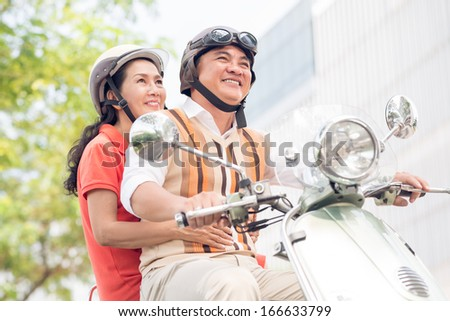 Angle view of modern cheerful seniors riding a scooter  - stock photo