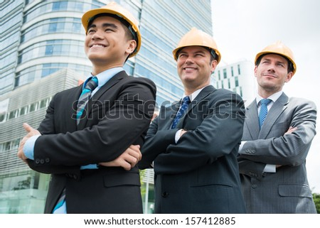 Angle view of professional engineers standing in a line on the foreground - stock photo