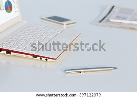 Angle View of Work Place with Laptop Pen and Business Newspaper on White Office Desk Table in Light Color Tones - stock photo