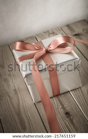 Angled shot of a gift box with closed lid, wrapped in silver paper and tied to a bow with a satin ribbon.  Placed on a weathered old wooden table. - stock photo