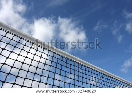 Angled tennis court net against cloudy sky