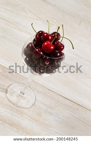 Angled vertical image of fresh black cherries in glass on aged wood - stock photo