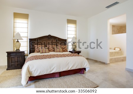 Angled view of bedroom with large windows and bright light source - stock photo