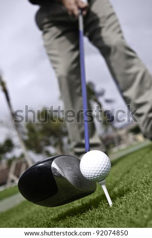 Angled view of golfer addressing golf ball on tee with driver. - stock photo