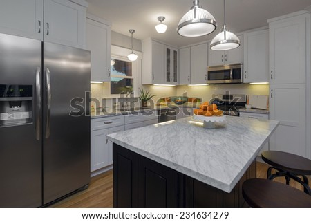 Angled view of luxurious white Kitchen in Modern Home with white Marble counter tops wooden floor and all new new stainless steel appliances. - stock photo