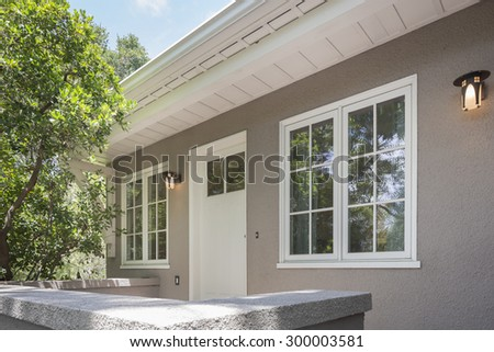 Angled view towards entry door with white framed windows and exterior lights.  - stock photo