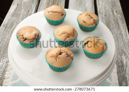 angled view white cake stand with fresh homemade blueberry whole wheat muffins on an old barn wood table - stock photo