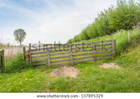 Angled wooden gate tied with rope in a rural area along a dike in springtime. - stock photo