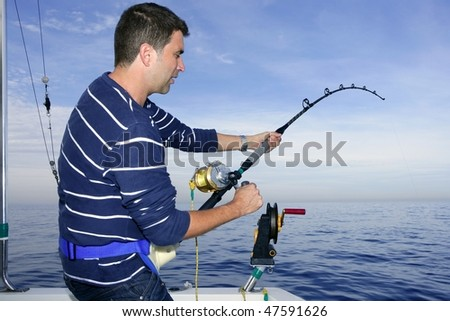 Angler fisherman fighting big fish rod and reel saltwater ocean - stock photo