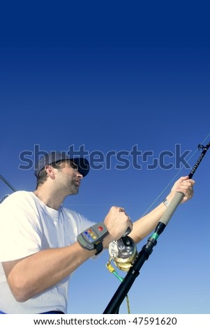 Angler fisherman trolling rod and reel fighting saltwater fish - stock photo