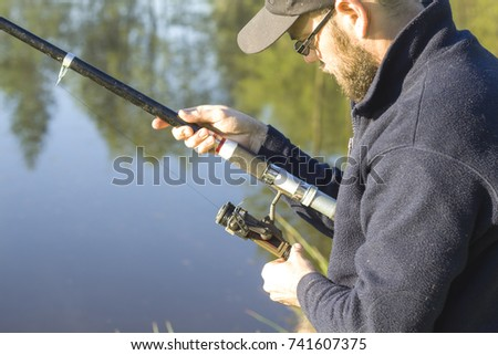 Angler in the hat stands with a fishing rod over the water and adjusts the brake on the spinning-wheel