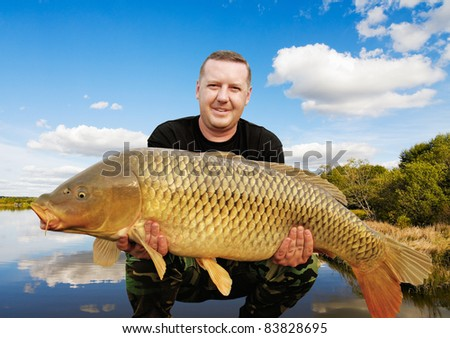 angler with carp to 32 pounds at sunset - stock photo