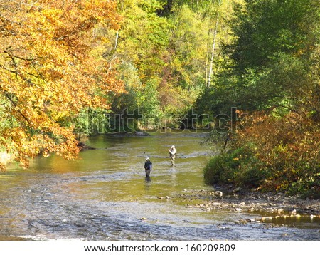 Anglers in the stream at autumnal scenery - stock photo