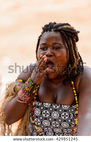 ANGOLA, LUANDA - MARCH 4, 2013:  Angolan sympathic woman makes the street performance of the national falk dance in Angola, Mar 4, 2013. Music is one of the main African entertainments.