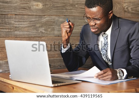 Angry African businessman is displeased with inefficiency in digital data. Irritated shot of man in round glasses sitting in cafe with official documents, checking information on up-to-date laptop. - stock photo