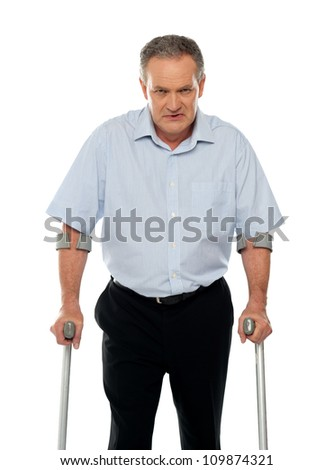 Angry aged man with crutches looking at you. All on white background - stock photo