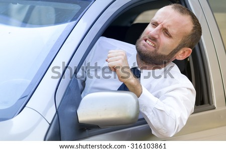 Angry and aggressive businessman in the car