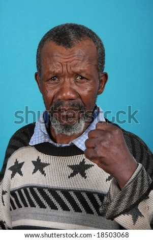 Angry and annoyed African man against blue background - stock photo