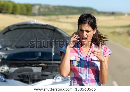 Angry and desperate woman calling to insurance assistance service after car accident. Upset woman on cellphone discussion explaining broken down auto engine. - stock photo