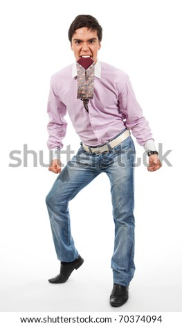 Angry and fierce looking man eating his tie, standing isolated on white