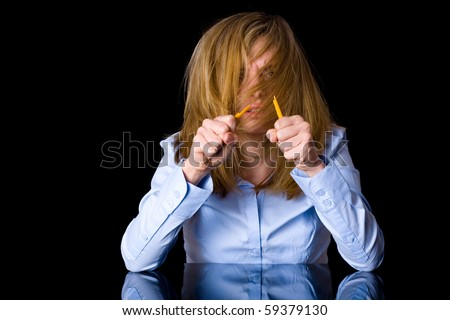 angry and stressed blonde businesswoman in blue shirt, studio shoot isolated on black background - stock photo