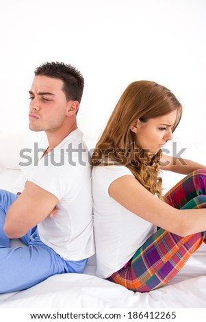 angry and upset couple in fight turning their back on each other in bed, domestic bedroom atmosphere - stock photo