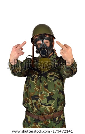 Angry Army Soldier with Green Helmet And Gas Mask Giving the middle finger - stock photo