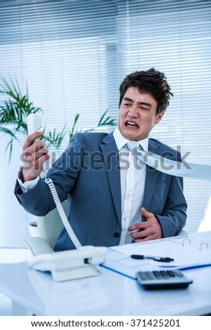 Angry asian businessman shouting on the phone in his office - stock photo