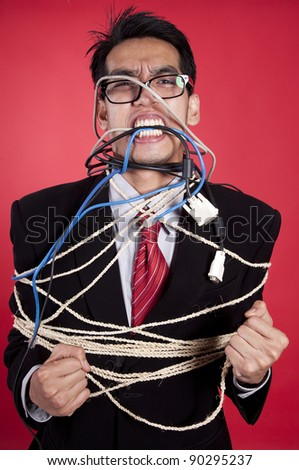 Angry Asian businessman tied up shot in studio over red background - stock photo