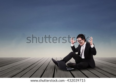 Angry Asian Businessman working on laptop - stock photo