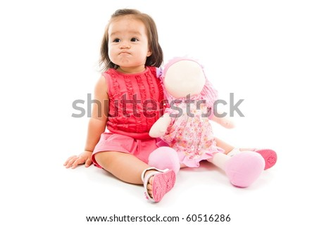 Angry Baby holding a doll on white backgroudn - stock photo