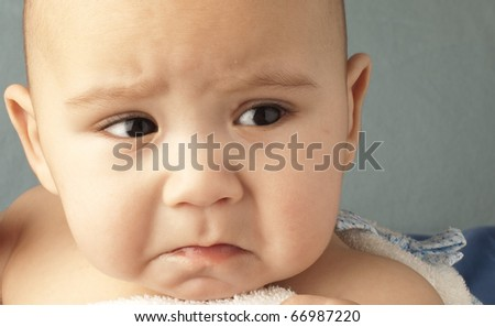 angry baby on a blue background closeup - stock photo