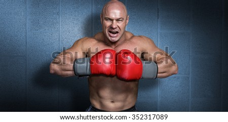 Angry bald boxer with punching gloves against dark grey room - stock photo