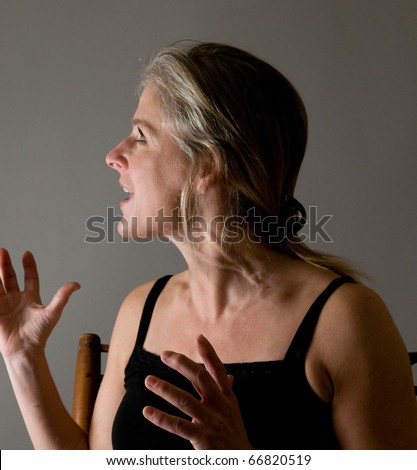 angry, battered woman (with bruises on throat) yelling at someone with disdain, defiance - stock photo