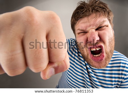 Angry bearded bandit punching you. Wide angle - stock photo