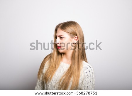 angry blonde girl looking to the side, isolated - stock photo