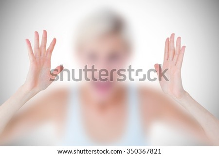 Angry blonde screaming with hands up against white background with vignette - stock photo