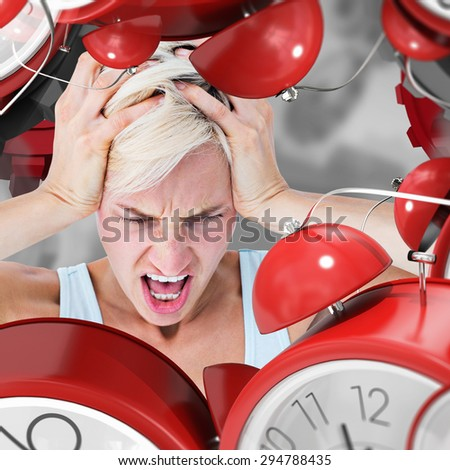 Angry blonde woman screaming and holding her head against grey vignette - stock photo