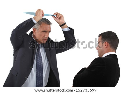 Angry boss about to hit employee with clip-board - stock photo