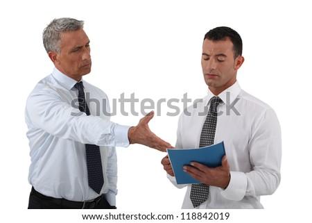 Angry boss displaying his displeasure to his employee - stock photo